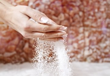 Woman pouring salt out of her hands while getting halotherapy treatment in salt room.